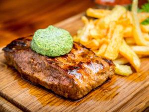 Steak de boeuf accompagné de beurre persillé et frites